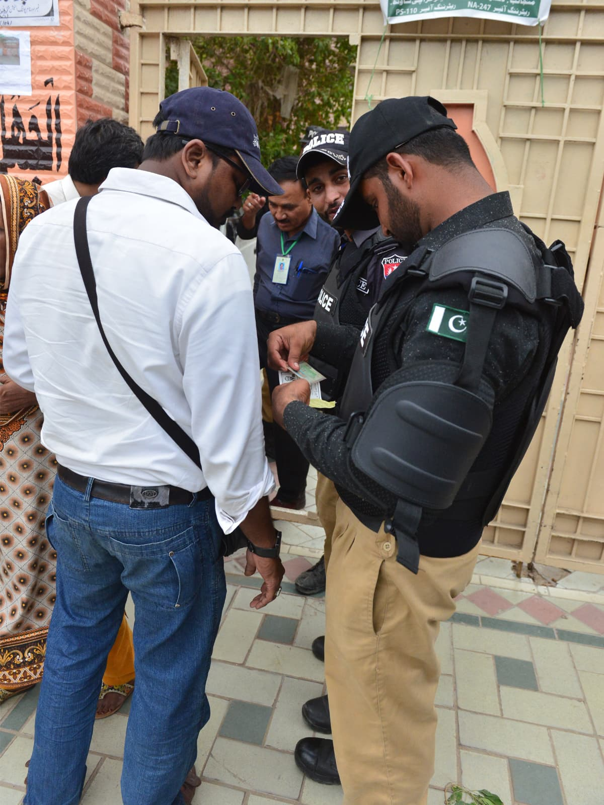 Police checking a voter's identity card at a polling station | Faysal Mujeeb, White Star