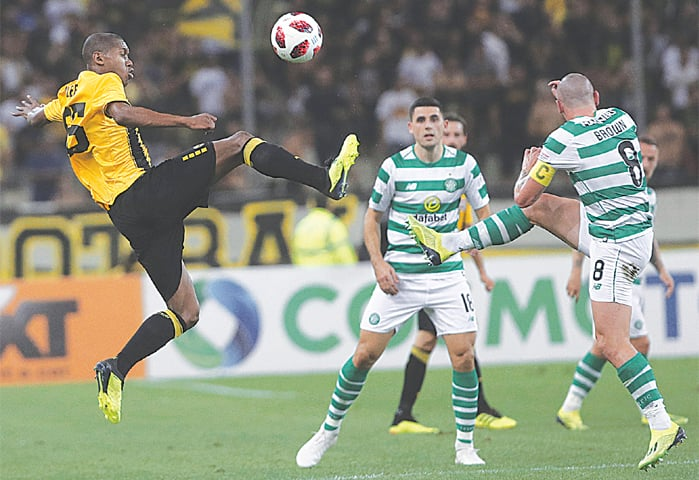 ATHENS: AEK Athens' Alef (L) battles for the ball with Celtic's Scott Brown (R) during the UEFA Champions League third qualifying round second leg at the Olympic Stadium.—AP
