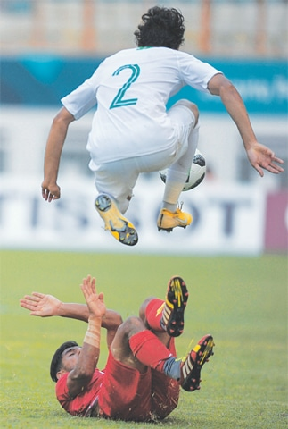 CIKARANG: Saudi Arabia's Abdullah Hassun Tarmin jumps over an Iran player during the group 'F' match on Wednesday.—AFP