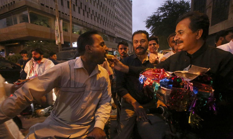 عمران خان کے وزیر اعظم منتخب ہونے پر کراچی میں پی ٹی آئی کے کارکنان مٹھائیاں تقسیم کر رہے ہیں — فوٹو: اے پی