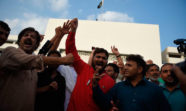 تحریک انصاف کے کارکنان و حامی پارلیمنٹ ہاؤس کے باہر عمران خان کے حق میں نعرے لگا رہے ہیں — فوٹو: اے ایف پی