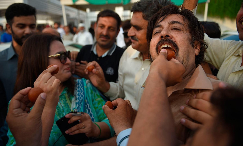 پی ٹی آئی کارکنان نے پارلیمنٹ کے باہر مٹھائی بھی تقسیم کی — فوٹو: اے ایف پی