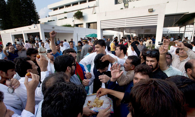 پی ٹی آئی کارکنان پارلیمنٹ ہاؤس کے باہر عمران خان کے حق میں نعرے لگا رہے اور مٹھائی تقسیم کر رہے ہیں — فوٹو: اے پی