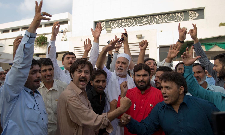 تحریک انصاف کے کارکنان و حامی پارلیمنٹ ہاؤس کے باہر عمران خان کے حق میں نعرے لگا رہے ہیں — فوٹو: اے پی