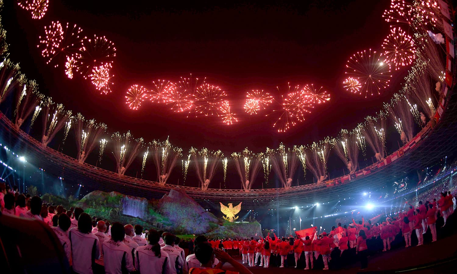 Delegates look up to witness a breathtaking fireworks display during the opening ceremony at the Gelora Bung Karno stadium in Jakarta. —AFP