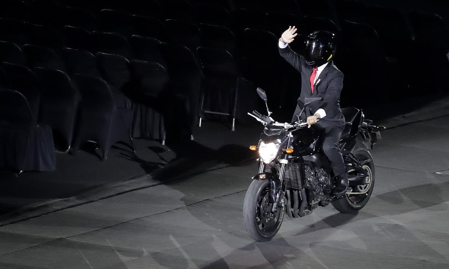 A helmeted rider representing President Joko Widodo doing stunts on a motorbike. —AP