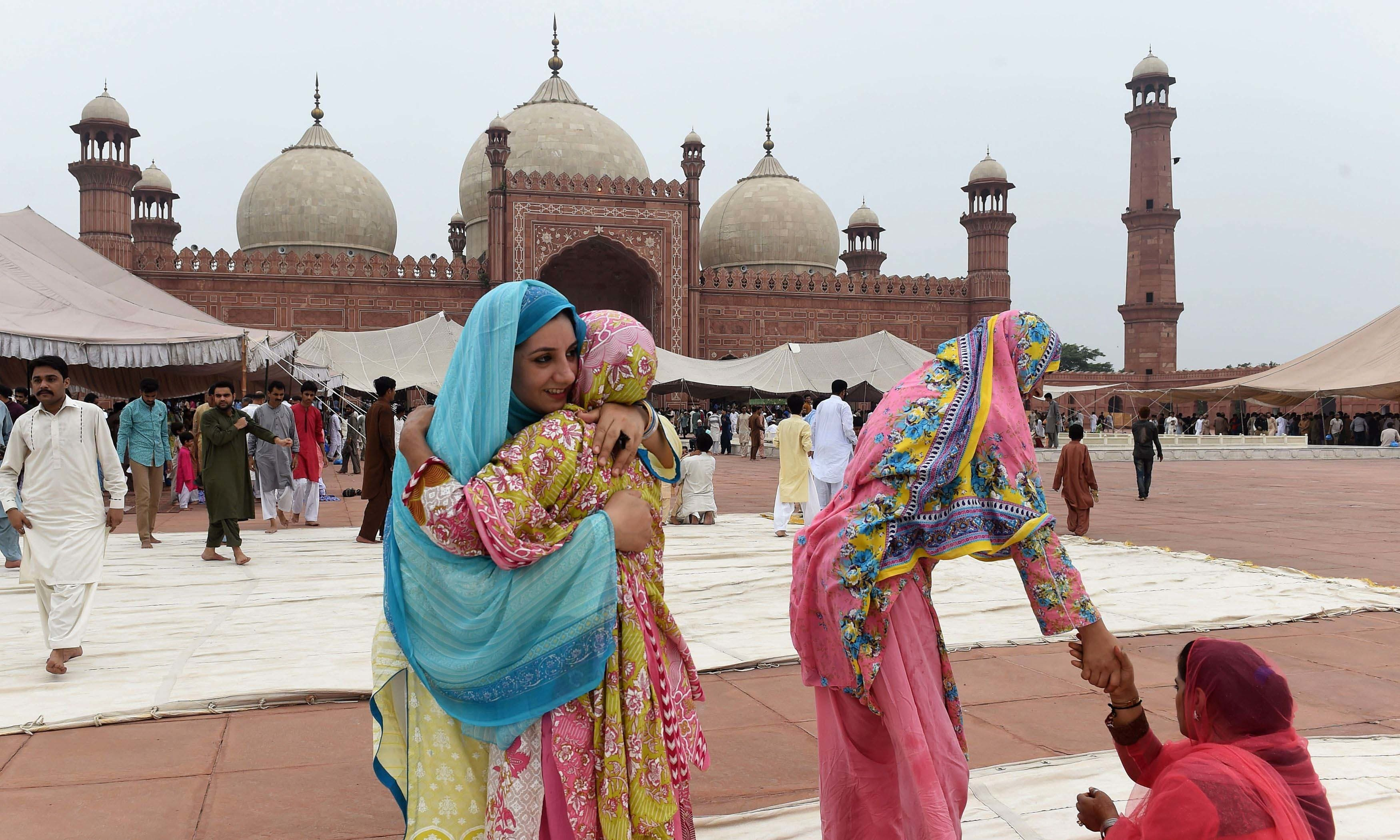 Women hug each other after Eid prayers. — AFP