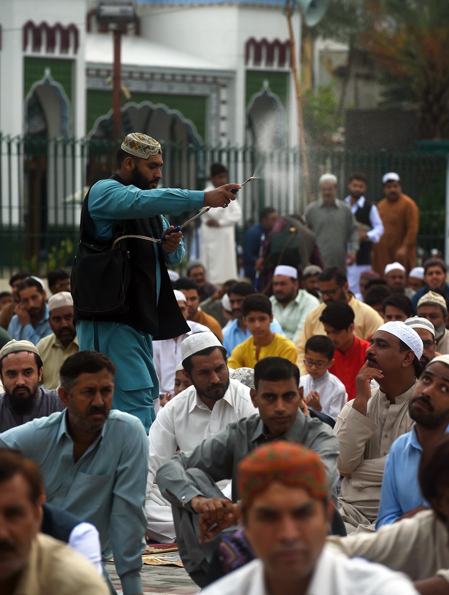 A man sprays perfume during Eid prayers outside a mosque in Rawalpindi. — AFP