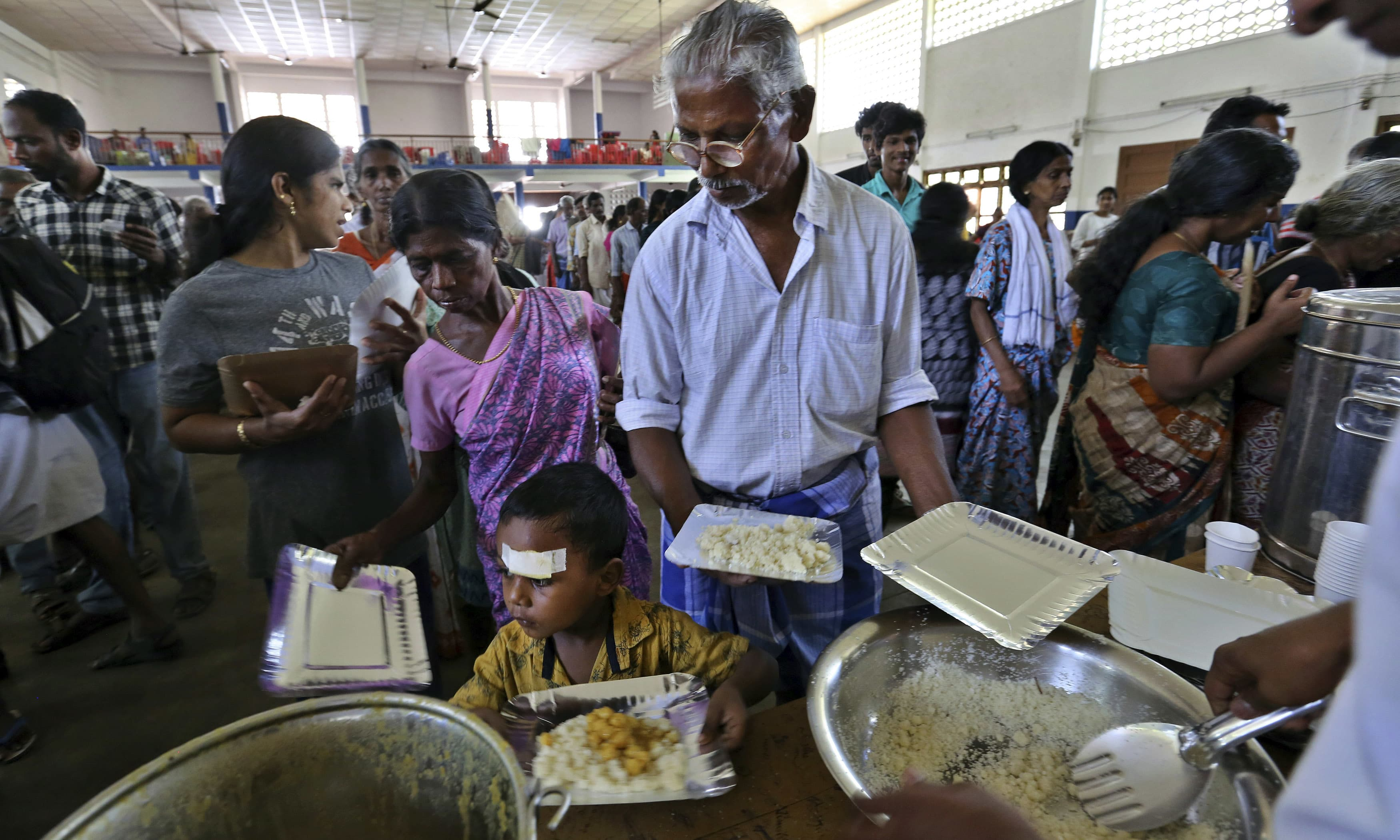 Flood affected people receive food at a relief camp set up inside a school in Kochi, in the southern state of Kerala. —AFP