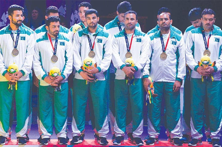 PAKISTAN'S kabaddi team poses on the podium with their bronze medals on Friday.—AFP