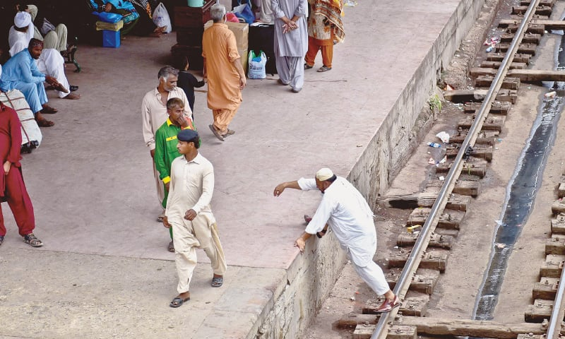 Avoiding the pedestrian bridge a man crosses the track while risking his life to get to another platform. / Photos by Fahim Siddiqi / White Star