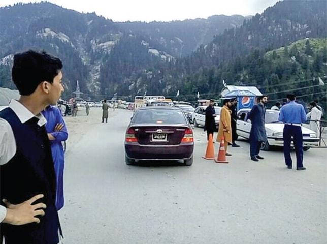 People wait for opening of Lowari tunnel in Upper Dir. — Dawn