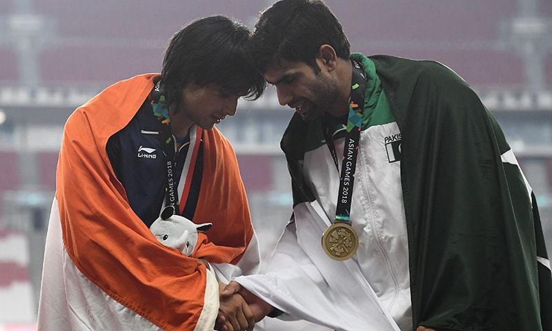 پاکستان ندیم ارشد سونے کا تمغہ جیتنے والے بھارتی ایتھلیٹ نیرج چوپڑا سے ہاتھ ملا رہے ہیں— فوٹو: اے ایف پی