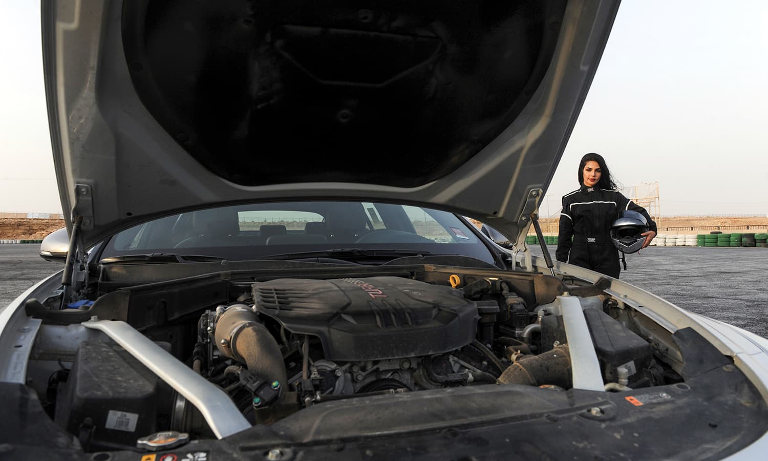 Rana Almimoni poses with her helmet next to her car on the track in Dirab motor park, on the southern outskirts of Riyadh. — AFP