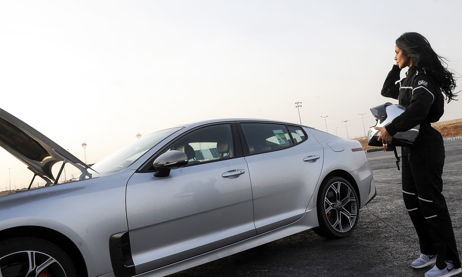 Rana Almimoni stands with her helmet next to her car on the track in Dirab motor park outside Riyadh. — AFP