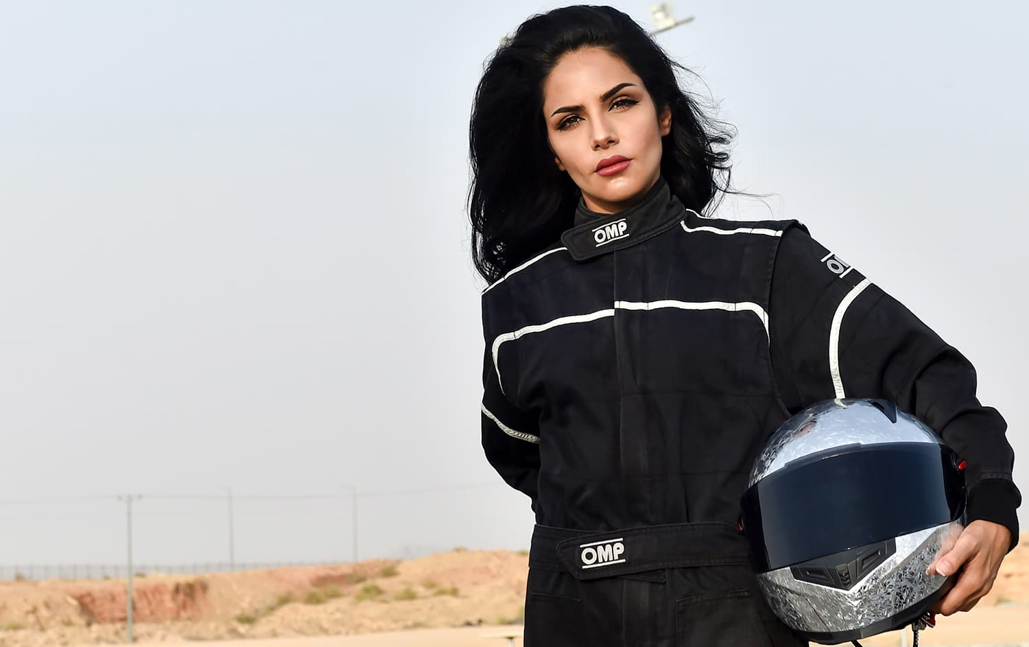 Rana Almimoni poses with her helmet on the track in Dirab motor park. — AFP