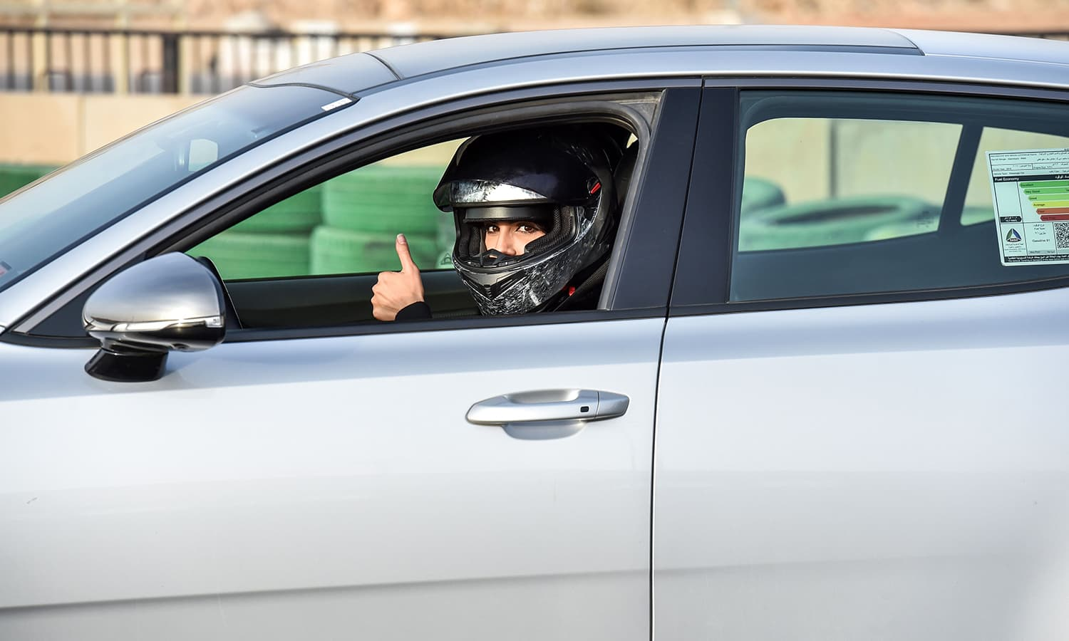 Rana Almimoni poses with the thumbs-up gesture in her car. — AFP