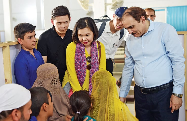 Members of a Thai delegation talk to Afghan refugees during a visit to Registration Card Modification Centre at Azakhel, Nowshera, on Tuesday. — Photo by Abdul Majeed Goraya