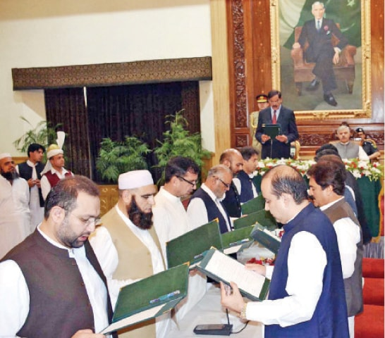 Acting KP Governor Mushtaq Ghani administers oath to the new cabinet members in Peshawar on Wednesday. — APP