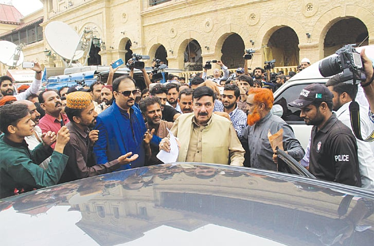 RAILWAYS Minister Sheikh Rashid speaks to people during his visit to the Cantt station on Thursday.—PPI