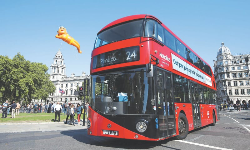 A large balloon depicting London Mayor Sadiq Khan in a yellow bikini floats over an iconic London red bus as demonstrators gather in Westminster, in central London, on Saturday.—AFP