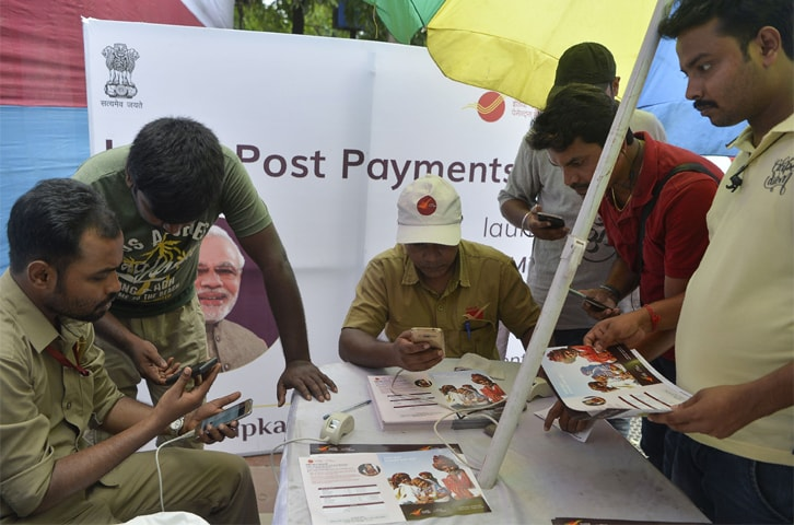 Indian post office employees help customers for opening new post office bank account 'India Post Payment Bank' in Siliguri on Saturday. India's Prime Minister Narendra Modi on September 1 launches the India Post Payments Bank (IPPB) across India. Customers are benefited with savings and current accounts using their mobile phones and aadhar card, also in rural areas.—AFP