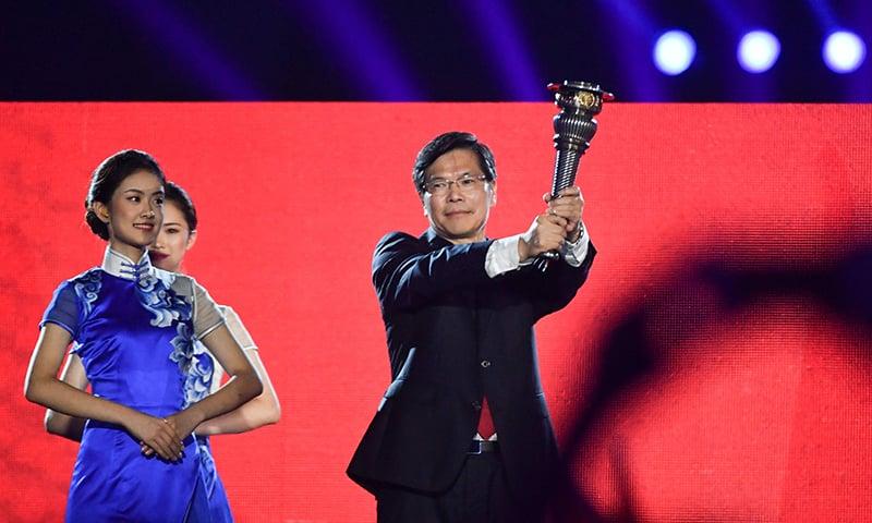 2022 ایشین گیمز کی میزبانی کرنے والے چین کے نمائندے ایشین گیمز کی مشعل تھامے ہوئے ہیں— فوٹو: اے ایف پی