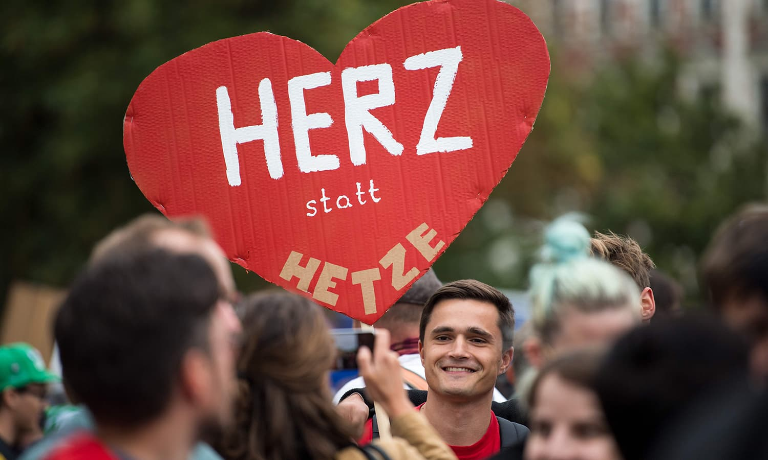 "A demonstrator holds up a heart-shaped poster reading ""Heart instead of agitation"" during a counter-march in Chemnitz. —AFP"