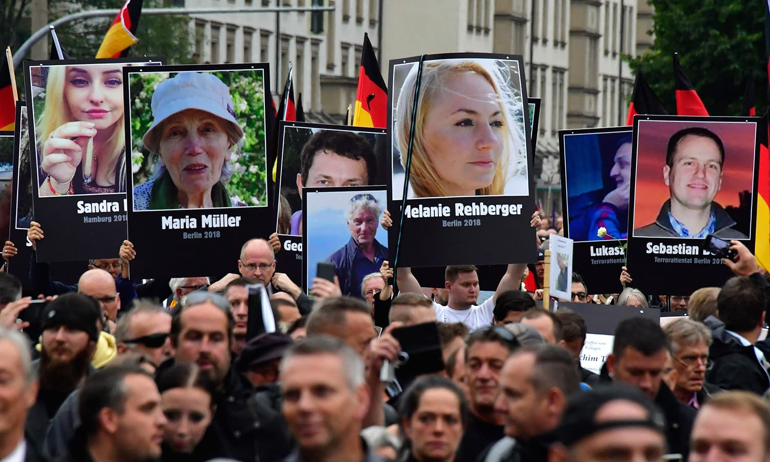 Demonstrators hold up placards showing portraits of victims of refugees during a protest organised by the far-right Alternative for Germany (AfD) party. —AFP