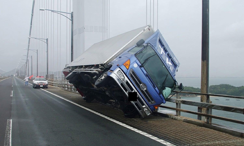 ظوفان کے دوران ہواؤں کی رفتار 216 کلومیٹر فی گھنٹہ تک کی شدت اختیار کرگئی جس کی وجہ سے ٹرک ترچھا ہوگیا —فوٹو: اے ایف پی
