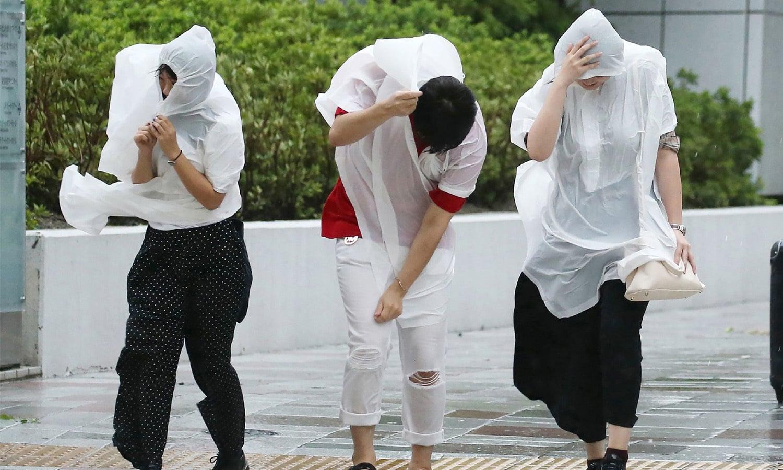 لوگ بارش سے بچنے کے لیے اپنے آپ کو برساتی سے لپیٹنے کی کوشش کررہے ہیں—فوٹو: اے ایف پی