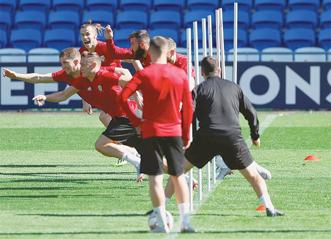 CARDIFF: Wales' Gareth Bale (top) attends a training session with team-mates at the Cardiff City Stadium on Wednesday for their Nations League match against Ireland.—Reuters