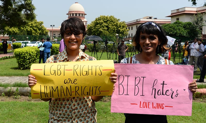Supporters and members of India's LGBT community hold up signs outside the Supreme Court. ─ AFP