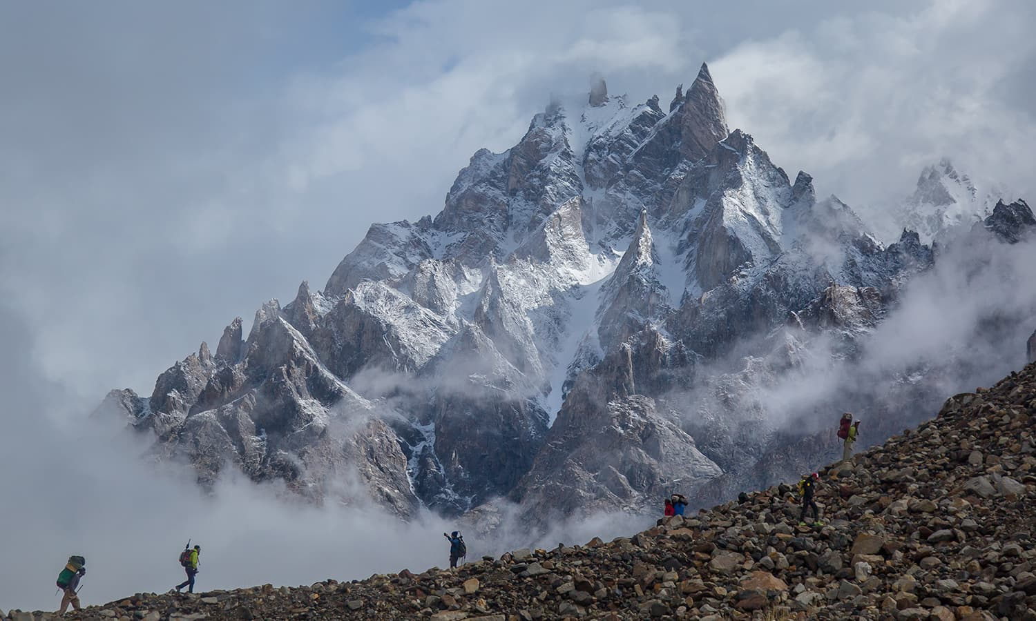 Climbers and porters try to find the trail after Urdukas with Lungka Group (6,250m) in the background.