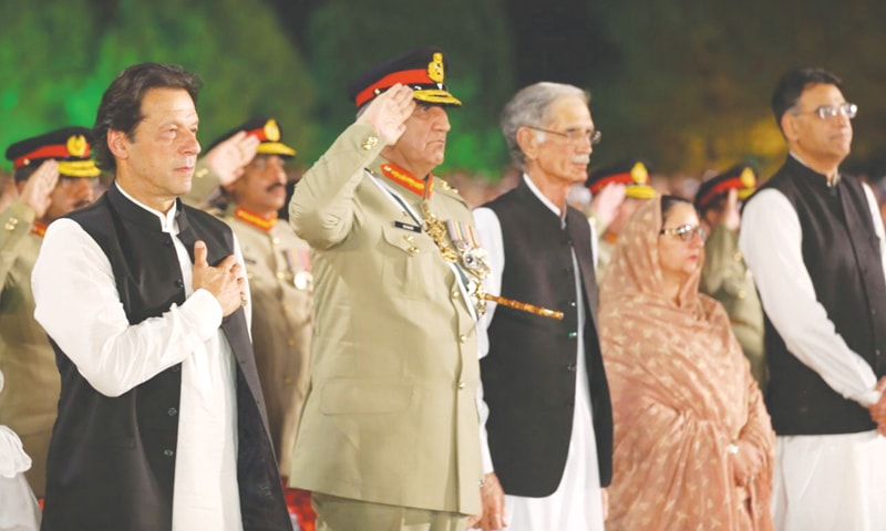 PRIME Minister Imran Khan and Chief of the Army Staff Gen Qamar Javed Bajwa listen to the national anthem during a ceremony held at the GHQ on Thursday to mark Defence and Martyrs Day.