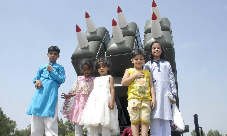 یومِ فضائیہ کے موقع پر پاکستانی بچے فوجی سازوسامان کے ساتھ تصاویر بنوارہے ہیں — فوٹو : آن لائن