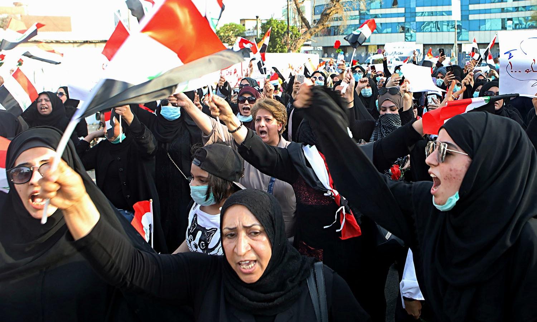 بصرہ میں ایرانی قونصل خانے کے باہر مظاہرین نے 'ایران باہر نکل جاؤ' کے نعرے لگائے جس کے بعد انہوں نے قونصل خانے پر حملہ کردیا اور ایرانی پرچم بھی نذرآتش کردیا  — فوٹو: اے پی