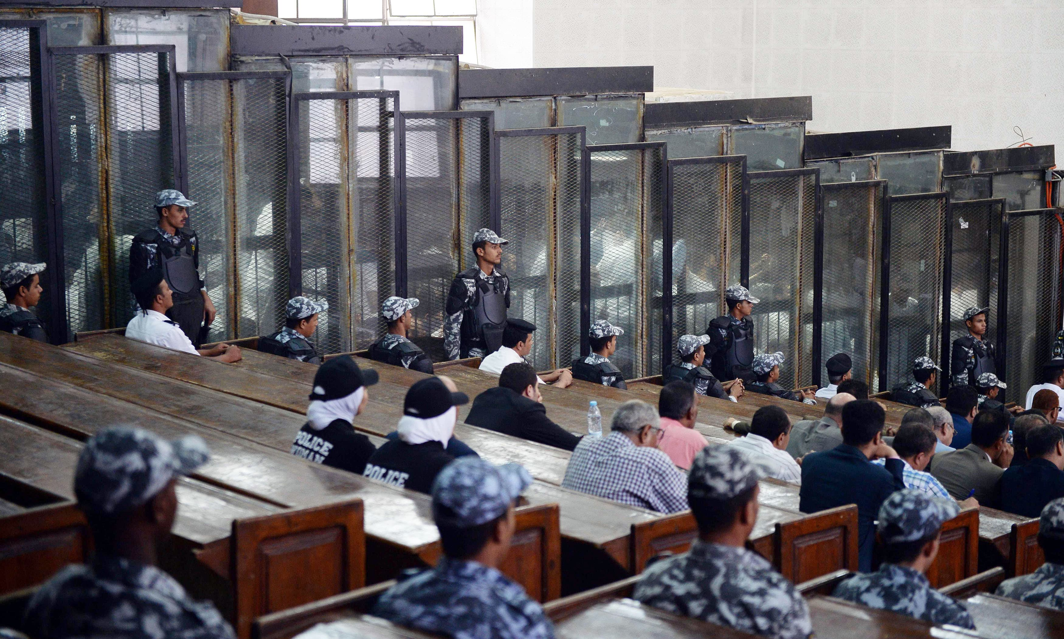 This picture shows the courtroom and soundproof glass dock (bottom) during the trial of Muslim Brotherhood members. —AFP
