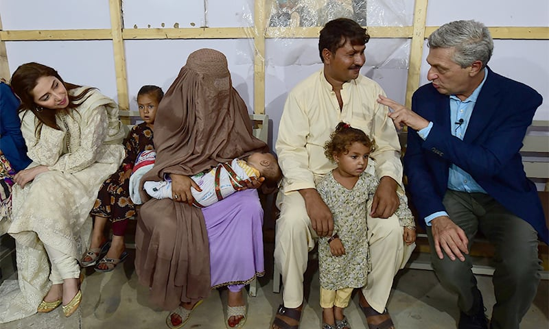 United Nations High Commissioner for Refugees Filippo Grandi (R) interacts with an Afghan refugee family at the Azakhel Voluntary Repatriation Centre as UNHCR advocate and actress Mahira Khan (L) looks on. ─ AFP