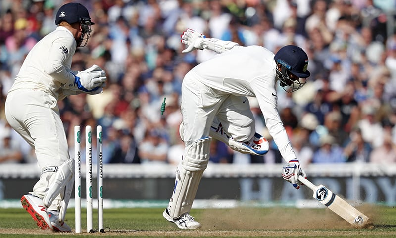 England's Jonny Bairstow (L) runs out India's Jasprit Bumrah (R) as the Indian Innings comes to a close. — AFP