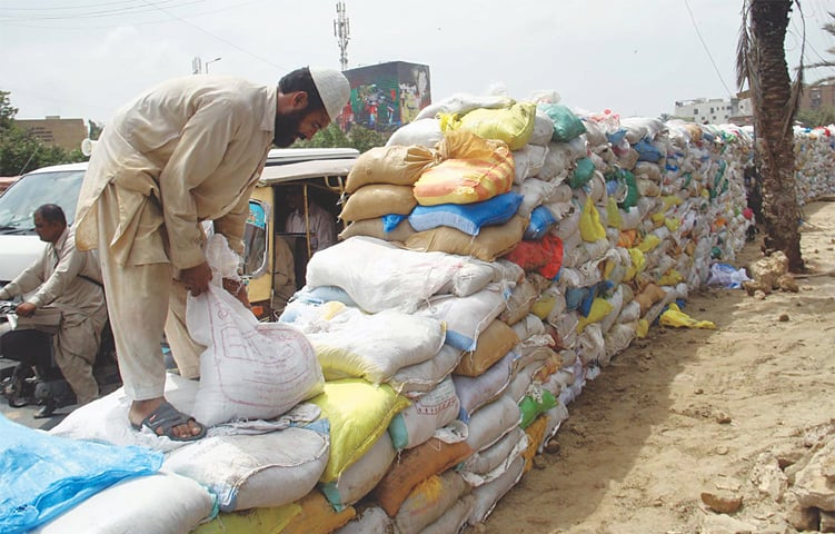 GRAVEL sacks being arranged on Monday to build a makeshift protective shield for security personnel, to be deployed at Numaish Chowrangi during the first 10 days of Muharram.—Online