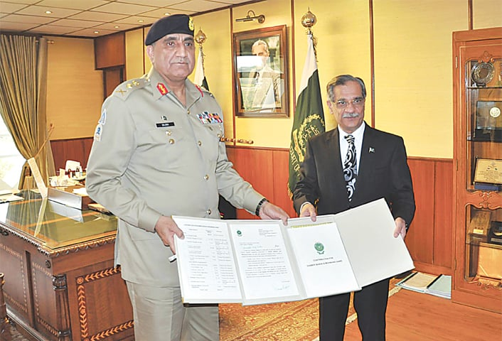 CHIEF of the Army Staff Gen Qamar Javed Bajwa presents a cheque for over Rs1 billion to Chief Justice of Pakistan Mian Saqib Nisar for construction of dams on Monday.—Online