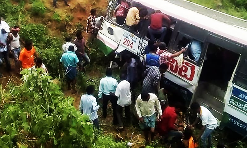 Onlookers and rescuers gather around a bus that crashed in Jagtial district in India's southern Telangana state.—AFP