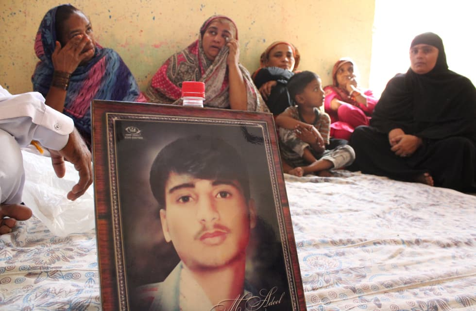 Bereaved mothers wipe away tears behind the portrait of Adeel, a victim of the fire | Photo by Danyal Adam Khan