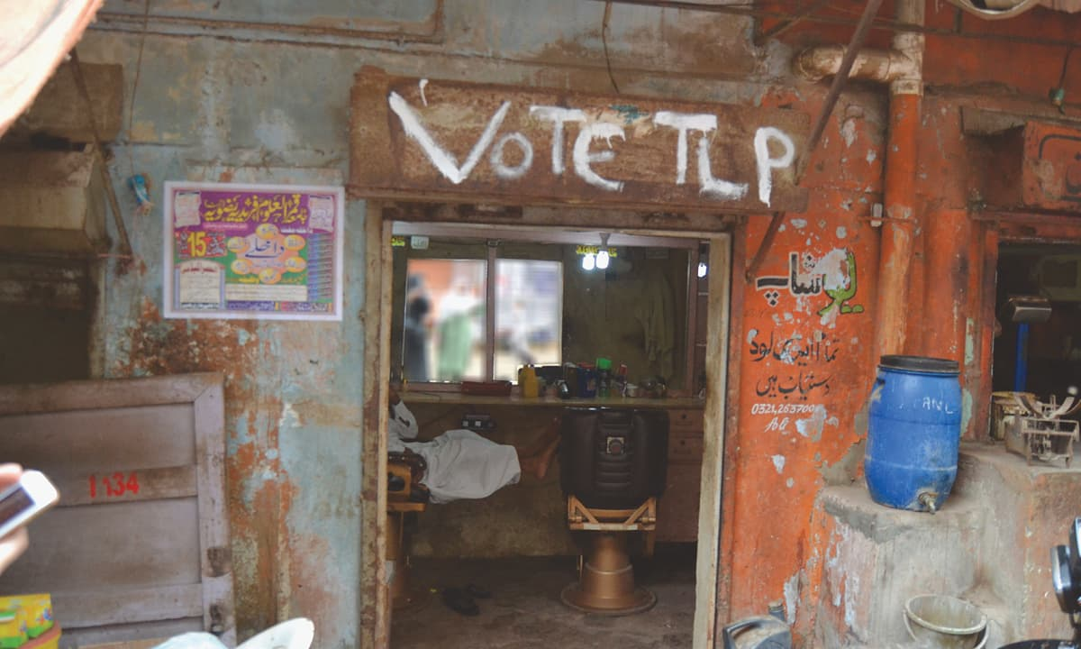 A Tehreek-e-Labbaik Pakistan campaign slogan on a barber shop in Lyari, Karachi | Momina Manzoor Khan