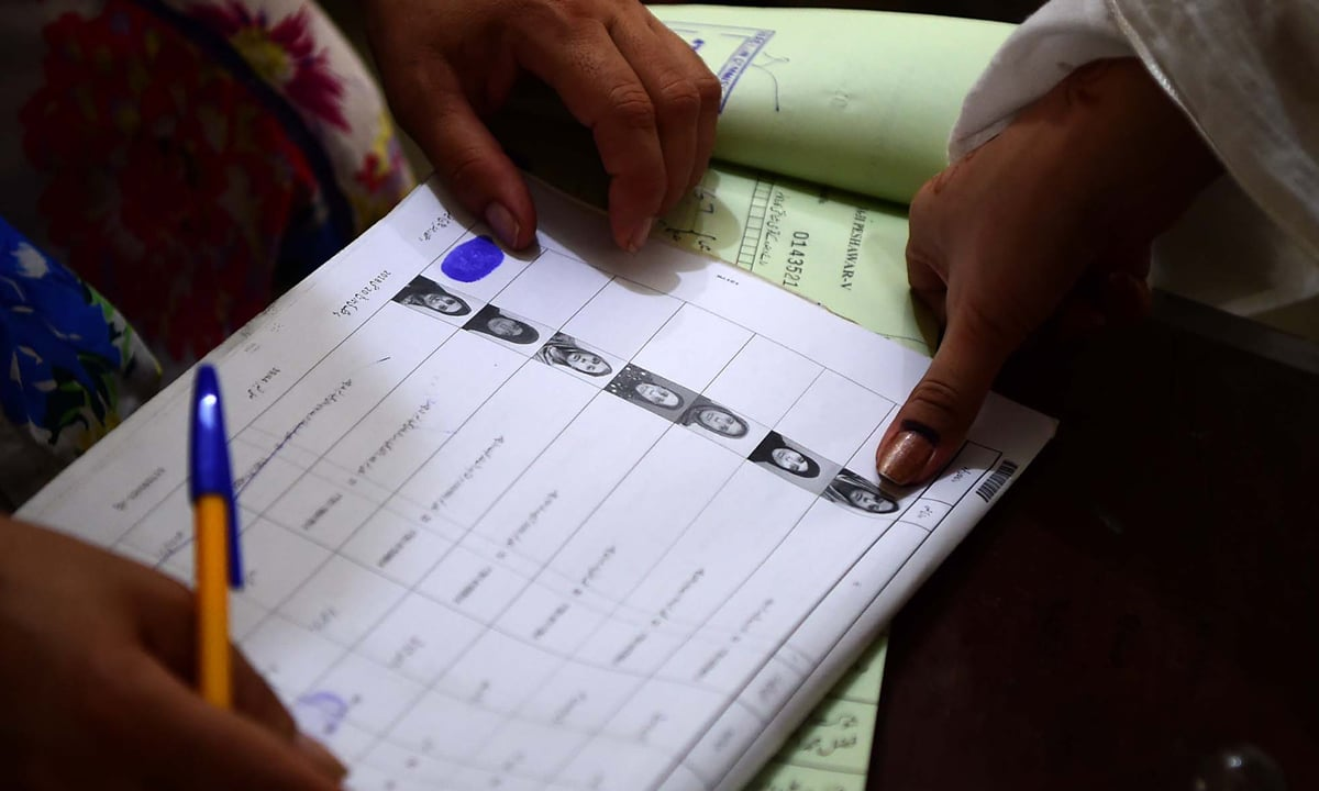 A female voter puts her thumbprint on her ballot in Peshawar