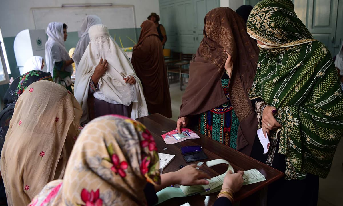Women voters passing through a polling booth in Peshawar