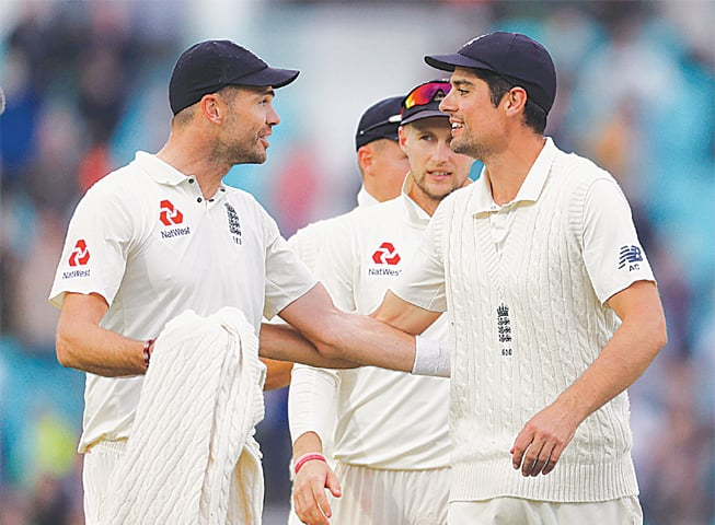ALASTAIR Cook (R) congratulates James Anderson for breaking Glenn McGrath's Test wickets record.—Reuters