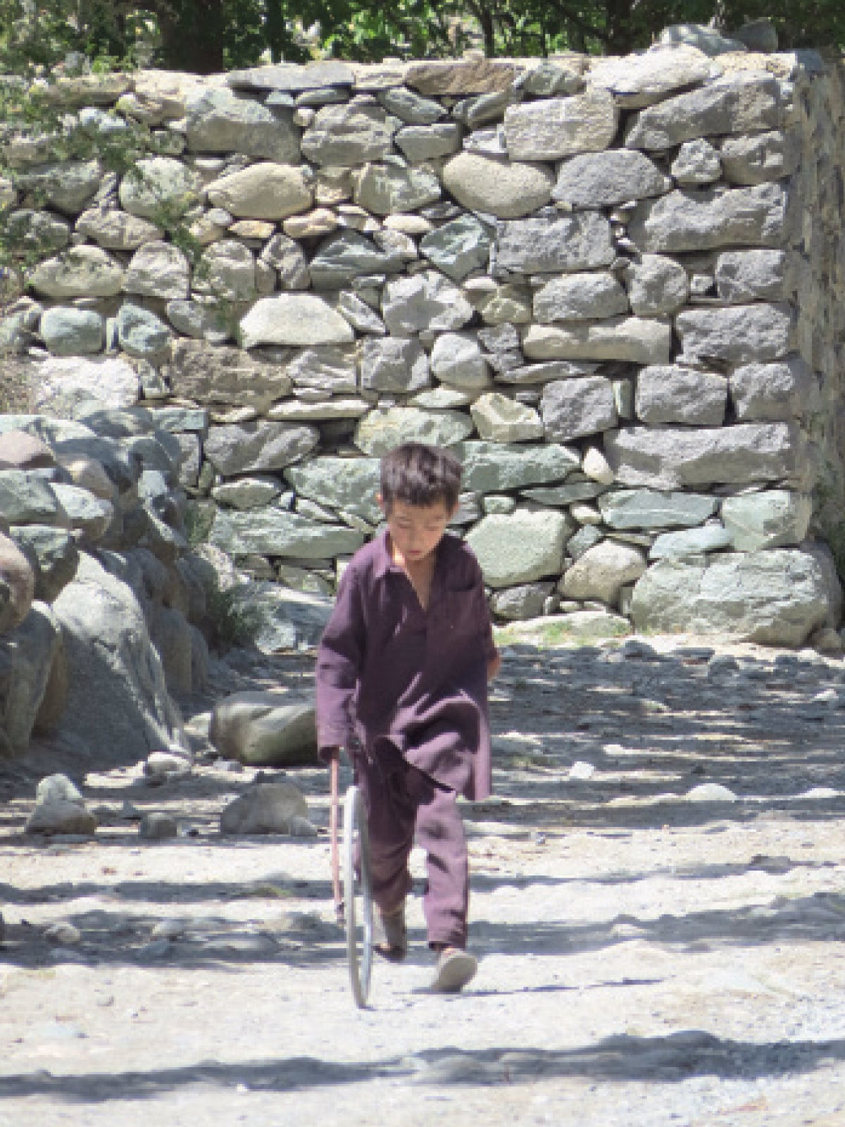 A child keeps himself occupied on the streets of Hatoon in Ghizer | Aurangzaib Khan