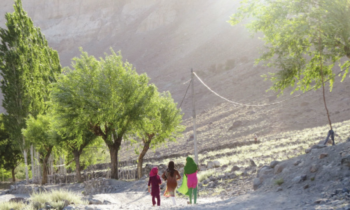 Little girls walk along a dirt track in Hatoon early morning | Aurangzaib Khan
